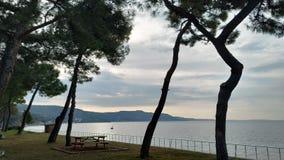 Sea coast on a calm day and cloudy sky. A calm day by the sea through the trees and cloudy sky Çanakkale stock image