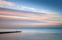 Sea coast, fisherman on the stone pier Stock Photos