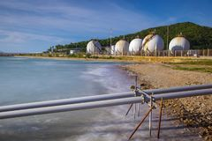 Sea coast and gas storage tank in heavy petrochemical industry e. State Stock Images