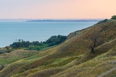 Sea coast with green hills. Summer landscap. City on the horizon.  stock photography