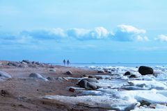 Sea coast line in haze with beach sand, ice, blue skies, clouds and city skyline on horizon. Royalty Free Stock Photos