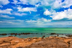 Sea coast line. Turquoise water, yellow sand and blue cloudy sky. Summer background Stock Image