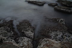 Sea coast in a long exposure shot, with blurred water Royalty Free Stock Photo