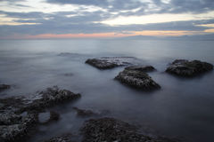 Sea coast in a long exposure shot at sunset, with blurred water Royalty Free Stock Image