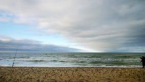 Sea. Coast, overcast sad day, autumn. Lone fisherman on the beach. Beats wave. Pleasant time for the fisherman stock photo