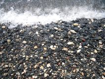 Sea coast, pebble and rashing foaming wave. Stock Image