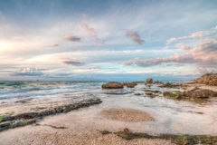 Sea coast with rocks and clouds Stock Photos