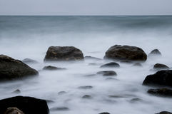 Sea coast with rocks and waves in motion blur. Sea coast with rocks and waves. Long exposure produces motion blur on the water Stock Photos