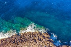 Sea coast on rocky beaches with turquoise water waves, aerial view.  stock photos
