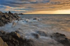 Sea coast after the storm at sunset. Royalty Free Stock Photography