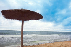 Sea coast with thatched umbrella Royalty Free Stock Image