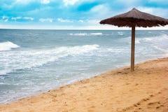 Sea coast with thatched umbrella Stock Photos