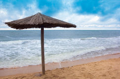 Sea coast with thatched umbrella Stock Images