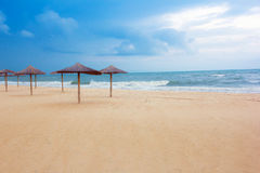 Sea coast with thatched umbrellas Royalty Free Stock Image
