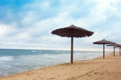 Sea coast with thatched umbrellas Royalty Free Stock Photos