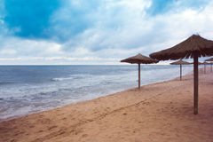 Sea coast with thatched umbrellas Royalty Free Stock Images