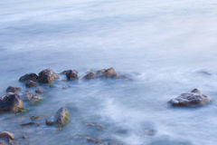 Sea coast with waves in motion blur. stock image