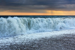 Sea coast with waves; sun appeared through clouds Royalty Free Stock Photo