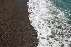 Sea coastline. Pebbles and water Stock Images
