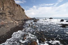 Sea coastline with foam, stones, pebbles and rocks Stock Photo