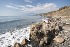 Sea coastline with foam, stones, pebbles and rocks Stock Photography