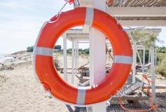 Sea Coastline with Life Preserver, gazebo and Beach Beds Stock Photos