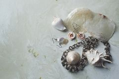 Free Sea Collection On Grey Marble Background. Seashell And Mother-of-pearl Earrings. Summer Jewelry. Metal Chain , Mother-of Stock Image - 154688481