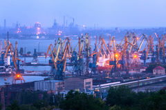 Sea commercial port at night against working steel plant. In Mariupol, Ukraine. Industrial landscape. Cargo freight ship with working cranes bridge in sea port royalty free stock images