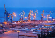 Sea commercial port at night in Mariupol, Ukraine. Industrial la. Ndscape. Cargo freight ship with working cranes bridge in sea port at dusk. Cargo port stock photos
