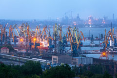 Sea commercial port at night in Mariupol, Ukraine. Industrial view. Cargo freight ship with working cranes bridge in sea port Royalty Free Stock Photo