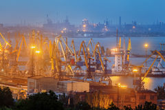 Sea commercial port at night in Mariupol, Ukraine. Industrial view. Cargo freight ship with working cranes bridge in sea port. Sea commercial port at night royalty free stock photos