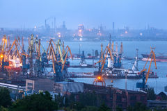 Sea commercial port at night in Mariupol, Ukraine. Industrial view. Cargo freight ship with working cranes bridge in sea port. Sea commercial port at night stock images
