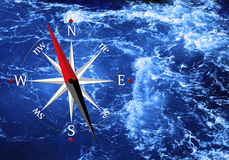 Sea and compass. Blue rippled water surface and a compass Royalty Free Stock Photography
