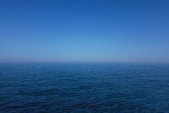 Sea. The contrast between blue sky and dark water Royalty Free Stock Image