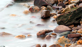 Sea crashing ober pebbled beach. The sea breaks over the pebbles. Exposure time has produced the misty effect of the water Royalty Free Stock Photo