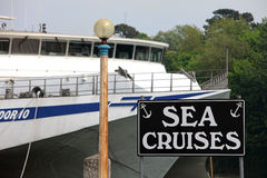 Sea Cruise Sign in Weymouth Dorset. Sign for sea cruises on black background with large ocean liner behind Royalty Free Stock Photos