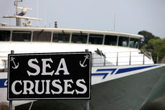 Sea Cruise Sign in Weymouth Dorset. Sign for sea cruises on black background with large ocean liner behind Royalty Free Stock Photography