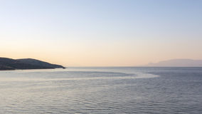 Sea Current. Wake of gentle ocean current shown in quiet water, Gulf of Corinth, Greece, pink dawn light Stock Images