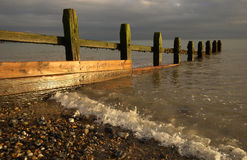 Sea defence groyne. A wooden sea defence groyne on a beach catches the setting suns rays Stock Photo