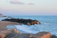 Sea defence. Rocks on a coastal beach line Royalty Free Stock Photo