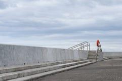 Sea defences. Coastal sea defences at Aberaeron, Wales, with lifebuoy and steps Stock Photos