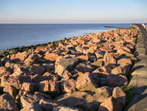Sea defences, Kent. Hampton pier sea defences, near Herne Bay and Whitstable, Kent, UK.  The late afternoon sun is glowing on the rocks. The Kentish Flats wind Stock Photography