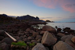 Sea at dusk in the Lofoten islands. Heap of rocks and sea at dusk in the Lofoten islands with a trunk deposited by the sea Stock Photography