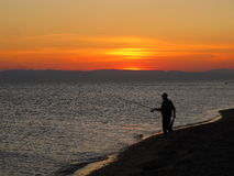 Sea,  evening, sunset, fisherman on the beach. Stock Images