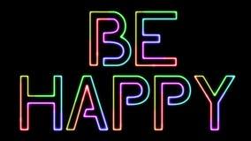 Sea feliz - el texto de neón de siete colores, luces móviles, en fondo transparente almacen de metraje de vídeo