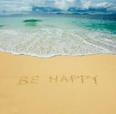 Sea feliz escrito en una arena Foto de archivo libre de regalías