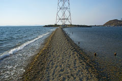 In the sea filled the road to the lighthouse, in the middle of the Sea Beach line passes. Mound in the sea Stock Photography
