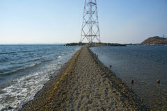 In the sea filled the road to the lighthouse, in the middle of the Sea Beach line passes. Mound in the sea Royalty Free Stock Image