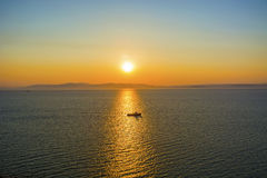 In the sea filled the road to the lighthouse, in the middle of the Sea Beach line passes. A ray of sunset, the sea floats a vessel sailing on the Gaza exactly a Stock Photography