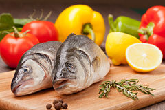 Sea fish prepared  for grill. Sea bass prepared to cooking on the background of vegetables and spices Stock Images